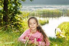 Славная девушка мечтая около реки на заходе солнца Стоковые Изображения RF