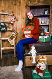 Славная девушка сидит в комнате с деревянными стенами Новый Год и Крис Стоковое Изображение