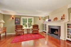 Славная живущая комната с винтажной мебелью и красным половиком Стоковые Изображения RF
