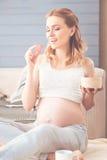 Славная красивая беременная женщина есть macaroons Стоковые Фотографии RF
