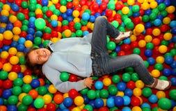 Славная маленькая девочка играя в бассейне с покрашенными пластичными шариками Стоковые Изображения