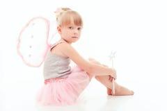 Славная маленькая девочка сидя на поле Стоковые Изображения