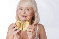 Славная услаженная женщина кладя 2 половины авокадоа совместно Стоковая Фотография