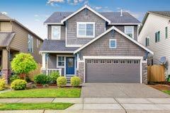 Славное воззвание обочины на двух уровнях дома, фасадной краски mocha и конкретной подъездной дороги Стоковые Фотографии RF