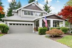 Славное воззвание обочины серого дома с крытым крыльцом и гаражом Стоковые Изображения RF