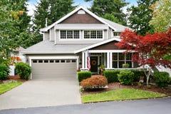 Славное воззвание обочины серого дома с крытым крыльцом и гаражом Стоковое фото RF