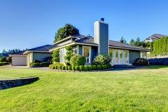 Славное воззвание обочины современного голубого дома с хорошо, который держат лужайкой Стоковые Изображения RF