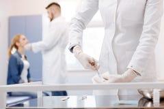 Славное профессиональное сотрудник военно-медицинской службы держа ножницы Стоковые Фотографии RF