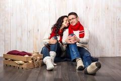 Славные пары влюбленности сидя на стиле рождества ковра Стоковые Изображения
