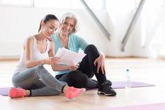 Славные приятные женщины читая план разминки Стоковая Фотография RF