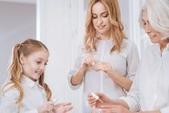 Славные усмехаясь женские члены семьи используя маникюр стоковое изображение