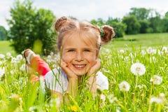 Славные улыбки девушки кладя на траву Стоковое Изображение RF