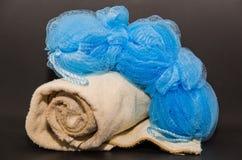 Славный взгляд крупного плана бежевого полотенца и голубой пушистой губки изолированных на темноте Стоковая Фотография RF