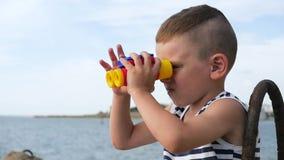 Славный мальчик в striped рубашке смотря через бинокли перед морем сток-видео