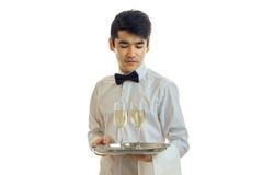 Славный молодой кельнер понизил его глаза вниз и держащ поднос с 2 стеклами вина Стоковые Фото