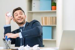 Славный работник играя с бумагой на таблице Стоковое Изображение