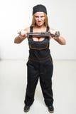 Славный сексуальный ключ удерживания механика женщины изолированный над белой предпосылкой Стоковое Фото