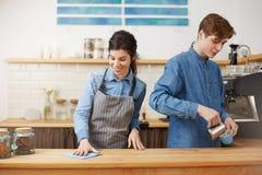 2 славных baristas работая на счетчике бара, смотря счастливый Стоковое Изображение RF