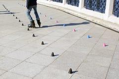 Слалом конькобежца ролика практикуя вдоль линии конусов Стоковые Изображения RF