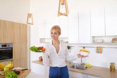 Сладостная женщина держит плиты в руках и проверяет свежесть сваренный Стоковые Изображения