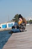 Сладостное курчавое предназначенное для подростков усаживание на краю порта Стоковые Фотографии RF