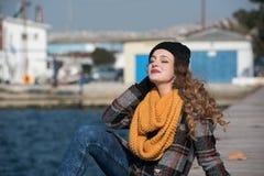 Сладостное курчавое предназначенное для подростков усаживание на краю порта Стоковая Фотография RF