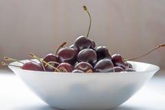 сладостные вишни на белом керамическом шаре Стоковое Изображение RF