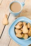 Сладостные вкусные печенья в голубой плите, чашке кофе с молоком Стоковые Изображения