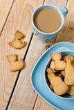Сладостные вкусные печенья в голубой плите, чашке кофе с молоком Стоковые Изображения RF