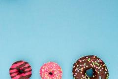 Сладостные очень вкусные donuts на голубой предпосылке Стоковое фото RF