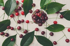 Сладостные свежие вишни с зелеными листьями на белой древесине Стоковая Фотография