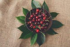 Сладостные свежие вишни с зелеными листьями на ткани мешка Стоковые Изображения