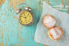 Сладостные слащавые donuts и винтажные часы на деревенской таблице Стоковые Изображения
