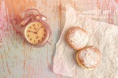 Сладостные слащавые donuts и винтажные часы на деревенской таблице Стоковое Фото