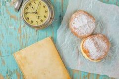 Сладостные слащавые donuts, книга и год сбора винограда хронометрируют на деревенской таблице Стоковое Фото