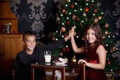 Сладостный давать детей высоко--5 пока ждущ Санту стоковая фотография