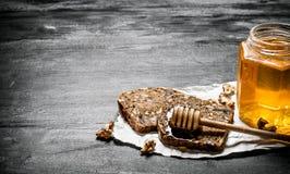 Сладостный мед в стеклянном хлебе опарника и плодоовощ с грецкими орехами стоковое изображение