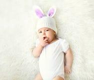 Сладостный младенец в связанной шляпе при уши кролика лежа на кровати стоковое изображение