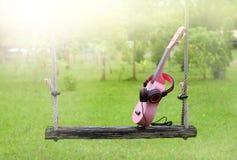 Сладостный пинк, наушники, музыка гавайской гитары на деревянном качании и зеленый цвет Стоковая Фотография