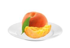 Сладостный сочный персик на белой плите изолированной на белизне Стоковое Изображение