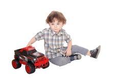 Сладостный трехгодовалый мальчик играя с его тележкой Стоковая Фотография