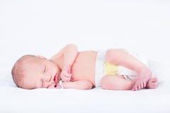 Сладостный newborn младенец спать на белом одеяле Стоковое Изображение