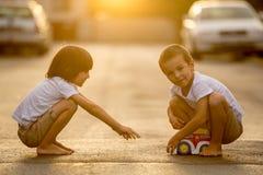 2 сладостных дет, братья мальчика, играя с автомобилем забавляются на s Стоковые Фото