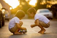 2 сладостных дет, братья мальчика, играя с автомобилем забавляются на s Стоковое фото RF