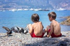 2 сладостных дет, братья мальчика, подавая голуби на пляже, Стоковые Изображения