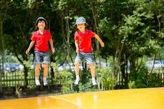 2 сладостных дет, братья мальчика, скача на большой батут Стоковая Фотография
