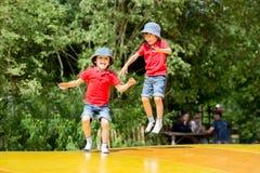 2 сладостных дет, братья мальчика, скача на большой батут Стоковые Изображения RF