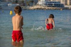 2 сладостных дет, брызгая один другого с водой на пляже Стоковые Изображения