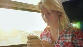 С вашим любимым прибором на дороге Женщина путешествует на поезде, используя smartphone сток-видео