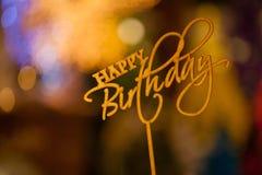 С днем рождения отправьте СМС ручка экстракласса знака на верхней части букетов запачканных в предпосылке bokeh Стоковые Изображения
